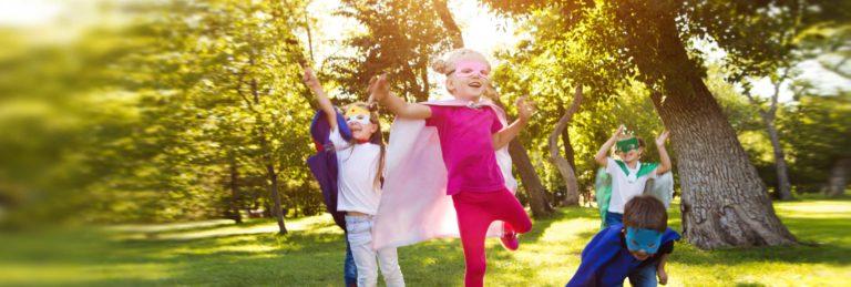 SoMA-Kinder in Superhelden-Kostümen laufen fröhlich über eine Wiese
